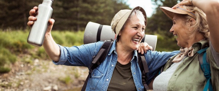 Two middle-aged woman smiling and hiking