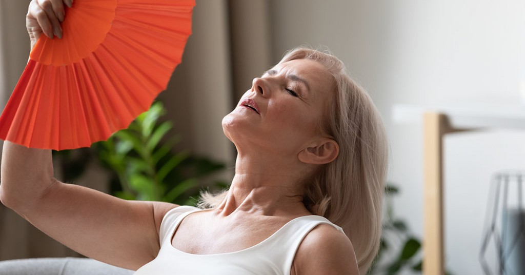 Middle-aged woman fanning herself
